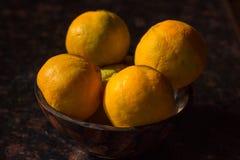 Las naranjas orgánicas desplumadas recientemente de granja se arreglan en un cuenco de madera aislado en un fondo negro imágenes de archivo libres de regalías