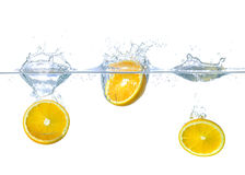 Las naranjas que caen en el agua con salpican Imagenes de archivo