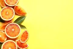 Las naranjas sangrientas frescas en el fondo del color, plano ponen con el espacio para el texto imagen de archivo