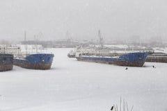 Las naves y las gabarras en el estacionamiento del invierno en el río Volga y cualquier pescador en nevada imagen de archivo libre de regalías