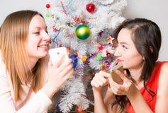 Las Navidades, dos chicas jóvenes sonrientes que mienten en la alfombra en el fondo un árbol de navidad iluminado foto de archivo libre de regalías