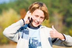 Las negociaciones del muchacho sobre el extremo del teléfono que muestra todo son ACEPTABLES Foto de archivo