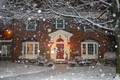 Las nevadas en casa hermosa del ladrillo con las columnas y las ventanas saledizas con el árbol de navidad se encienden para arri imágenes de archivo libres de regalías