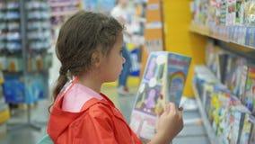 Las niñas compran libros en el supermercado almacen de metraje de vídeo