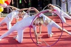 Las niñas con el baile del aro para el mundo bailan día en cuadrado de ciudad Foto de archivo libre de regalías