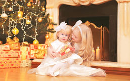 Las niñas de los niños con las cajas de regalo acercan al hogar del árbol de navidad y de la chimenea Imagen de archivo libre de regalías
