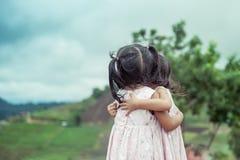 Las niñas del niño dos se abrazan con amor en el parque Imagenes de archivo