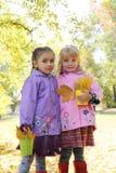 Las niñas en capas impermeables y las botas en otoño parquean Fotos de archivo libres de regalías