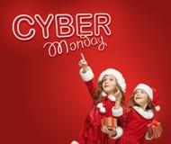 Las niñas en el sombrero de Papá Noel con los regalos Imagen de archivo libre de regalías