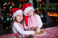 Las niñas en los sombreros de Papá Noel cuecen el pan de jengibre Fotos de archivo