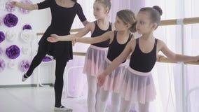 Las niñas están teniendo lección del ballet clásico que aprenden los movimientos de la pierna con el profesor en estudio del arte almacen de video