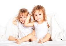 Las niñas felices hermanan a la hermana en cama debajo del combinado divirtiéndose foto de archivo libre de regalías
