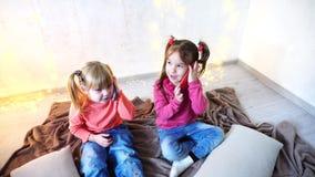 Las niñas felices utilizan los smartphones para el entretenimiento y se sientan en piso en sitio brillante con la guirnalda en la metrajes