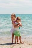 Las niñas hermosas (hermanas) juegan en la playa Imagen de archivo