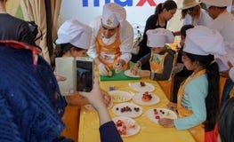 Las niñas que llevan los sombreros del cocinero están aprendiendo hacer cocinero imagen de archivo libre de regalías