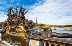 Las ninfas de la jábega doraron la estatua en el puente de Alejandro III con la torre Eiffel en el fondo en París foto de archivo