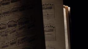 Las notas de la música del vintage con el rayo de la luz en negro, leva se mueven al ascendente izquierdo, cercano metrajes