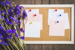 Las notas en blanco sobre el corcho suben con el ramo seco de la flor, vagos de madera imagen de archivo