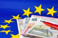 Las notas euro y el lápiz rojo, UE señalan por medio de una bandera Imagen de archivo libre de regalías