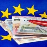 Las notas euro y el lápiz rojo, UE señalan por medio de una bandera Imágenes de archivo libres de regalías