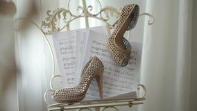Las notas musicales de los zapatos hermosos nupciales de la boda sobre el lujo de papel se inclinaron el primer almacen de video