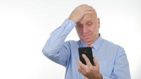 Las noticias decepcionadas de Read Cellphone Bad del hombre de negocios hacen gestos de mano nerviosos foto de archivo