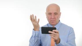 Las noticias decepcionadas de Reading Cellphone Bad del hombre de negocios hacen gestos de mano nerviosos imagen de archivo