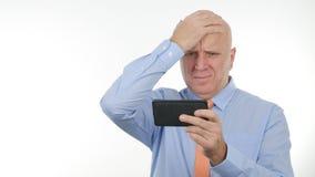 Las noticias decepcionadas de Reading Cellphone Bad del hombre de negocios hacen gestos de mano nerviosos foto de archivo