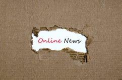 Las noticias en línea de la palabra que aparecen detrás del papel rasgado Imagenes de archivo