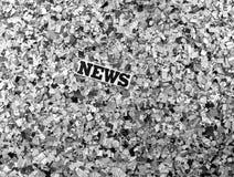Las noticias firman adentro una pila de confettii del periódico en monocromo Fotos de archivo libres de regalías