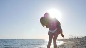 Las novias alegres ríen en la orilla del océano, muchachas con deportes metrajes