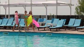 Las novias en bañador van a lo largo del embarcadero de madera en la piscina del fondo con agua azul, mujeres jovenes metrajes