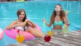 Las novias en trajes de baño soplan burbujas de jabón en la piscina, cóctel, muchachas hermosas en la reclinación del bañador almacen de metraje de vídeo