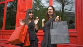 Las novias felices bailan después de compras acertadas con las bolsas de papel durante viernes negro almacen de metraje de vídeo