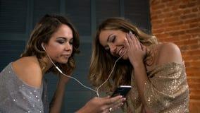 Las novias felices escuchan la música del teléfono y de la risa a cámara lenta metrajes