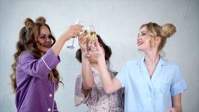 Las novias jovenes celebran el partido de pijama y bailan con champán en sus manos almacen de video
