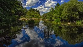 Las nubes blancas en el cielo azul se reflejan en el río Imágenes de archivo libres de regalías
