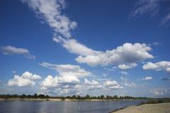 las nubes Blanco-coas alas en el cielo y dos kajaks flotan lejos en distancia en el río Foto de archivo libre de regalías