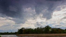 Las nubes de fuertes lluvias se nublan la acción sobre los cielos sobre el lago antes de una tormenta del verano metrajes