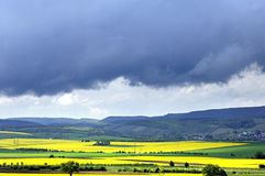 Las nubes de lluvia tiran sobre campos y montañas de la rabina Imagen de archivo