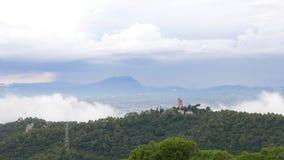 Las nubes de Timelapse vuelan sobre el castillo de Turo del Puig y las montañas boscosas almacen de metraje de vídeo
