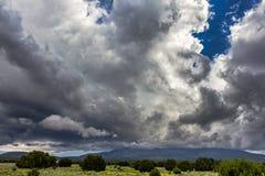 Las nubes de tormenta oscuras sobre las montañas acercan a la asta de bandera imágenes de archivo libres de regalías