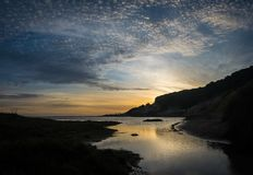 Las nubes del sol poniente y del puffball reflejaron en la laguna en la playa imagen de archivo