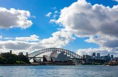 Las nubes enormes billow sobre el puente y el teatro de la ópera, iconos del puerto del horizonte del ` s de Sydney foto de archivo