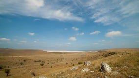 Las nubes flotan sobre los campos y el lago seco