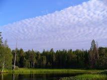las nubes inusuales aprietan el cielo sobre el bosque en la orilla del río Imágenes de archivo libres de regalías
