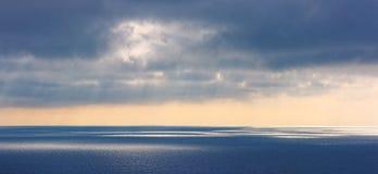 Las nubes mágicas sobre el mar alisan la superficie Foto de archivo