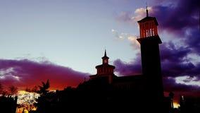 Las nubes misteriosas en la oscuridad como puesta del sol bañan el chapitel de la iglesia en luz anaranjada imágenes de archivo libres de regalías