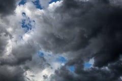 Las nubes oscuras, voluminosas cubren el cielo azul Él ` s que va a llover imagenes de archivo