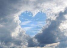 Las nubes oscurecieron los cielos con el cielo-corazón azul Fotos de archivo